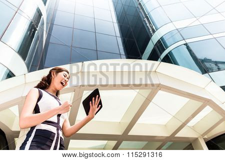 Asian businesswoman checking outside mails on tablet computer in front of tower building