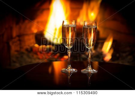 Two glasses of sparkling white wine in front of warm fireplace. Romantic, cozy relaxed magical atmosphere near fire. Valentines day concept