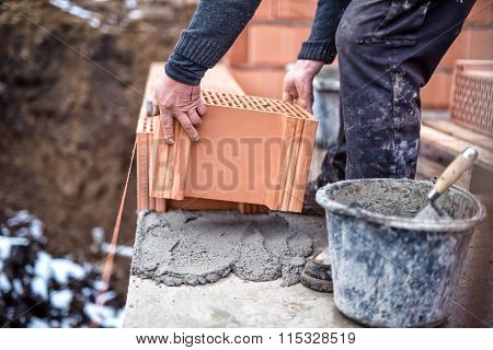 Construction Site Of New House, Worker Building The Brick Wall With Trowel, Cement And Mortar