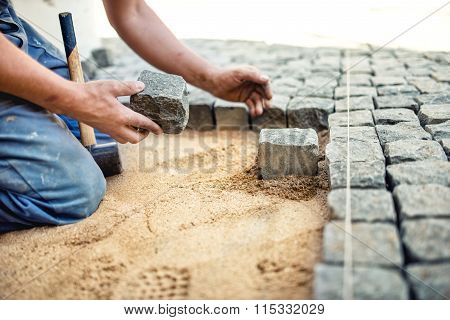 Construction Worker Placing Stone Tiles In Sand For Pavement, Terrace. Worker Placing stones