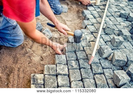Paving Pavement With Granite Stones, Workers Using Industrial Cobblestones For Paving Terrace