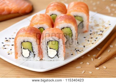 Sushi roll with smoked salmon, avocado, soft cheese and sesame seeds