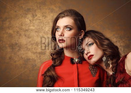 Two Beautiful Women In Red Dresses. Perfect Makeup And Hairstyle