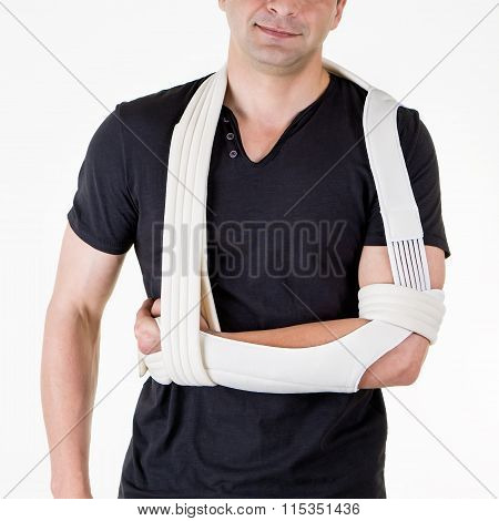 Mid Section Close Up of Man with Arm Supported in Modern Cast Sling and Standing in Studio with White Background poster