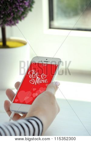 Smartphone with romantic screensaver  in female hand, on light background