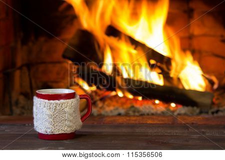 Cup of hot drink and fireplace as background. Christmas or winter warming drink.