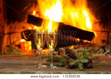 Two glasses of sparkling white wine and fir branches in front of warm fireplace. Romantic, cozy relaxed magical atmosphere near fire. New Year or Christmas concept