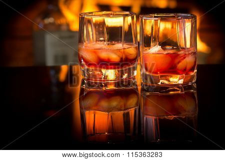 Two glasses of alcoholic drink wine in front of warm fireplace. Magical relaxed cozy atmosphere near fire