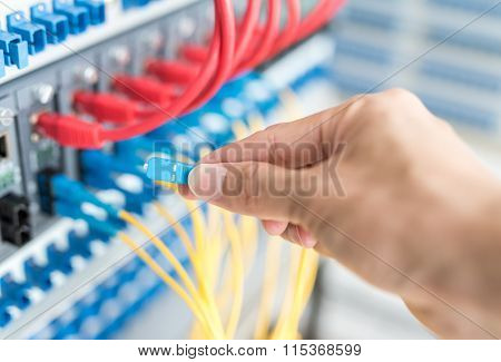hand with fiber network cables connected to servers in a datacenter