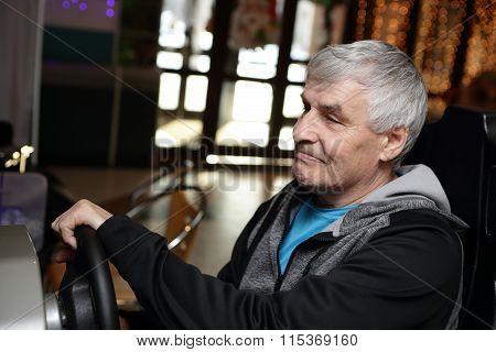 Senior Man Playing Arcade Game Machine
