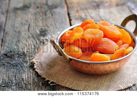 Dried apricot in a copper bowl on the old wooden background