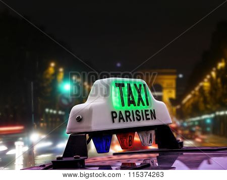 Closeup of Parisian taxi cab against the blurred Champs Elysees at night, Paris, France