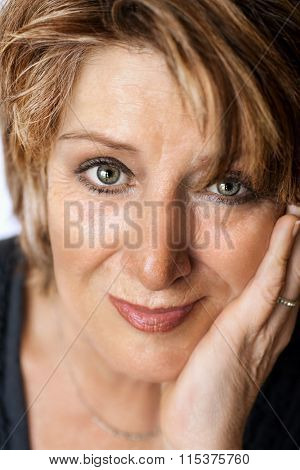 Senior lady with very nice eyes looking relaxed at camera with hand on chin