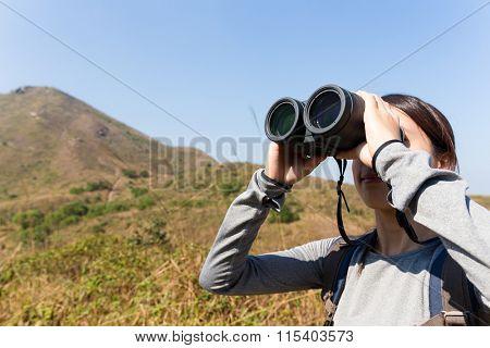 Woman looking though binocular when going hiking