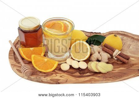 Cold and flu healing drink with vitamin c tablets, orange, lemon, ginger and cinnamon spice on olive wood board over white background. poster