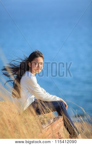 Portrait Of Asian Girl Relaxing Emotion Sitting In Grass Field And Windy Evening Use For Teen Age Le