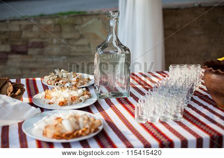 Traditional Ukrainian Wedding Feast Table At Reception: Vodka Bottle, Snacks And Glasses On Embroide