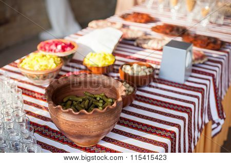 Traditional Ukrainian Wedding Feast Table At Reception: Snacks And Pickles In A Clay Pot On Embroide