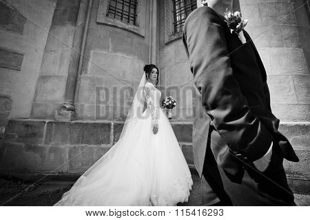 Sensual Brunette Bride In Vintage White Dress And Handsome Groom Posing Near Old Cathedral B&w