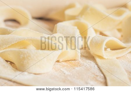 Fettuccini Pasta Dough In Flour With A Rolling Pin For Cooking