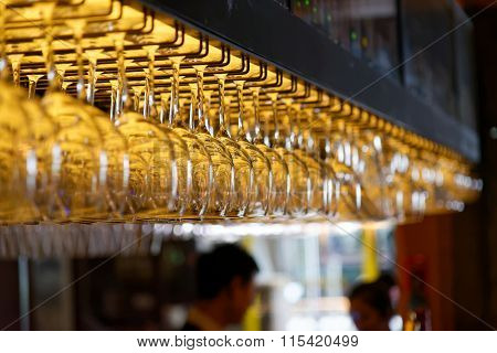 Group Of Empty Wine Glasses Hanging From Metal Beams In A Bar