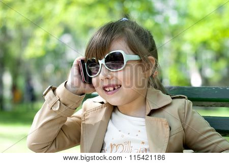 Smiling little girl in talking on cell phone