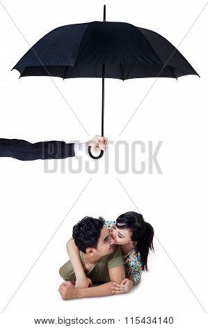 Happy Couple Kissing In Studio Under Umbrella