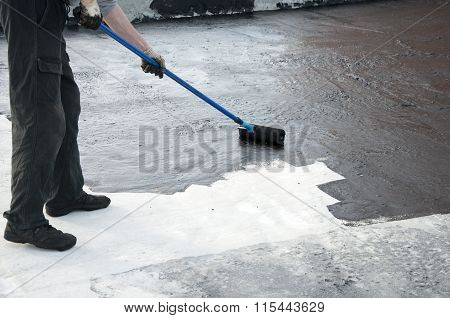 Roofer Worker Painting  Bitumen Praimer At Concrete Surface By The Roller Brush,  Waterproofing