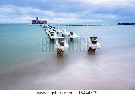 Frozen wooden breakwaters line to the world war II torpedo platform at Baltic Sea, Babie Doly, Poland poster