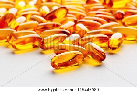 Biological additives to food vitamins for a healthy lifestyle capsules an omega 3 with cod-liver oil transparent orange color an embankment on a light background close up
