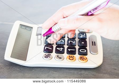 Woman's Hand With A Calculator And A Pen