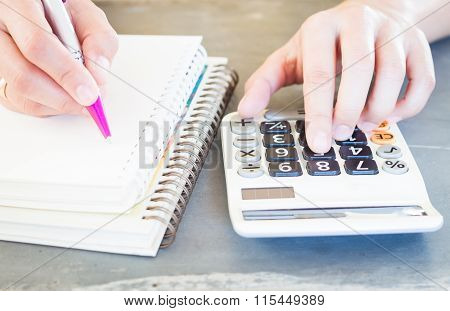 Hand Holding Pen And Pressing Calculator Buttons
