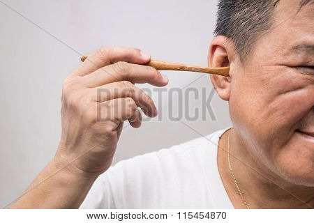 Man Un-hygienically Cleaning Ear Using Wooden Stick