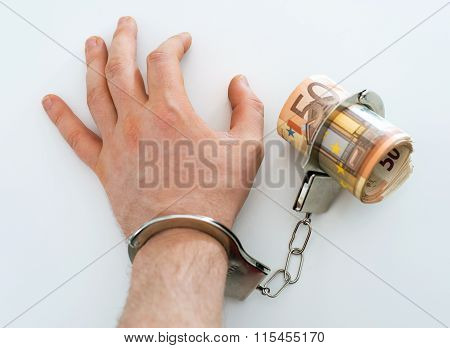 Hand with handcuffs and money. Bribery concept. ** Note: Shallow depth of field