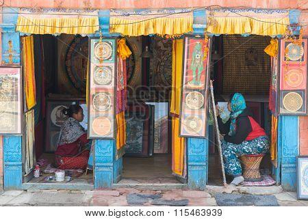 KATHMANDUNEPAL -DECEMBER 24 2015 : Unidentified Nepali women making handmade cloth painting in shop in tourist attraction area in KathmanduNepal on December 24 2015