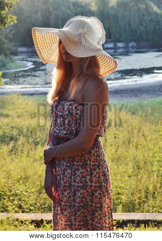 Young beautiful blond woman in summer hat with long hair smiling mischievously