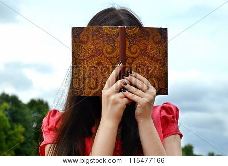 Shy brunette woman hiding behind a notebook