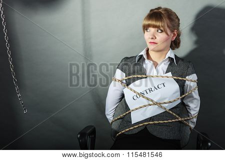 Upset businesswoman bound by contract terms and conditions. Helpless woman tied to chair become slave. Human shadow in background. Business and law concept. poster