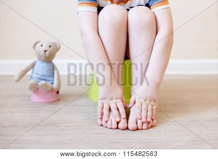 closeup of legs of the child sitting on the potty