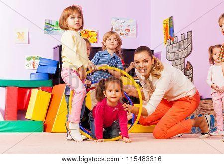Active game in kindergarten kids go though hoops