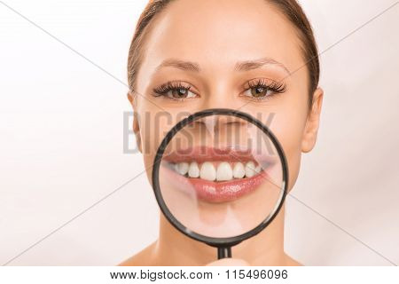 Young girl is holding a loupe at her mouth.