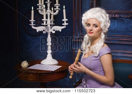 Woman In Historic Baroque Style Dress And White Wig With A Recorder In Their Hands