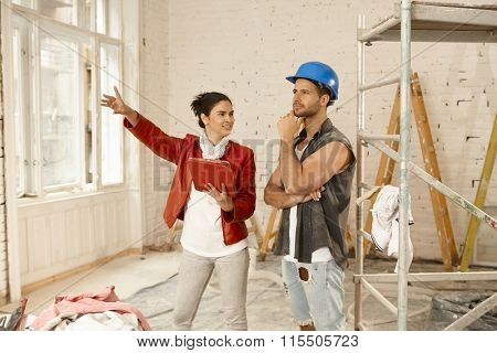 Female client and contractor talking at renovation site.
