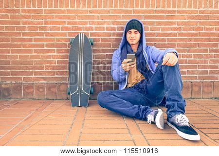 Young Man With Mobile And Skateboard Sitting On Brick Wall - Teenage Skater Guy Using Smartphone
