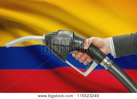 Fuel Pump Nozzle In Hand With National Flag On Background - Colombia