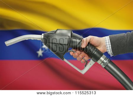 Fuel Pump Nozzle In Hand With National Flag On Background - Venezuela