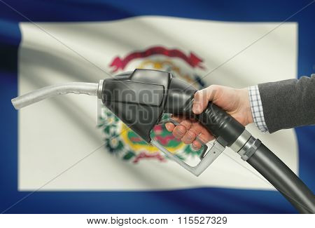 Fuel Pump Nozzle In Hand With Usa States Flags On Background - West Virginia
