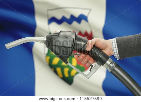 Fuel Pump Nozzle In Hand With Canadian Provinces Flags On Background - Northwest Territories