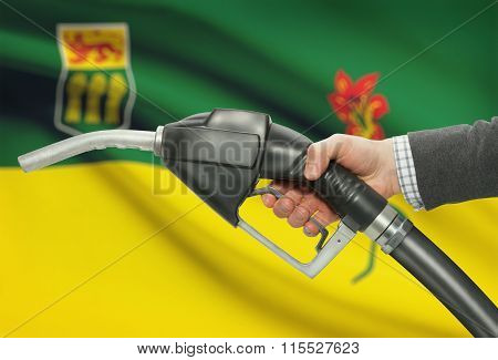 Fuel Pump Nozzle In Hand With Canadian Provinces Flags On Background - Saskatchewan