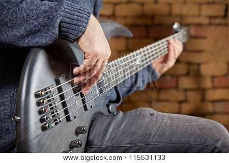 Bassist Is Playing The Bass In Front Of Brick Wall